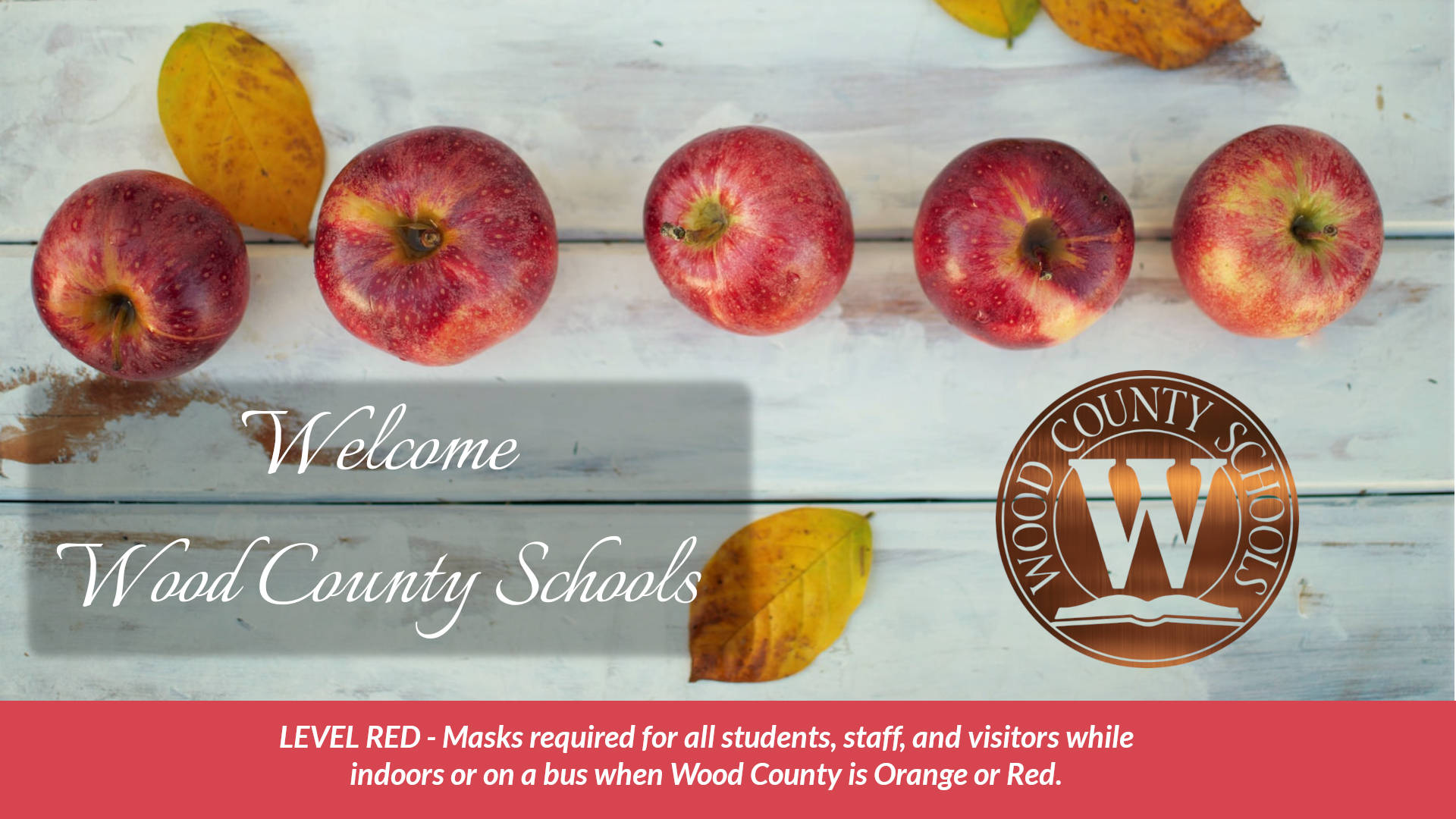 welcome to wood county schools with red apples and fall colored leaves