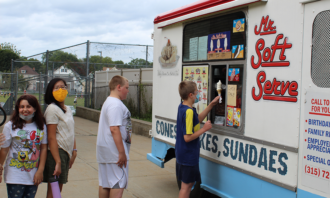 students in line at ice cream truck outdoors