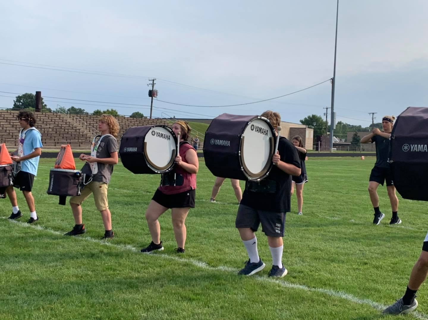 Students  outdoors carrying and playing large drums