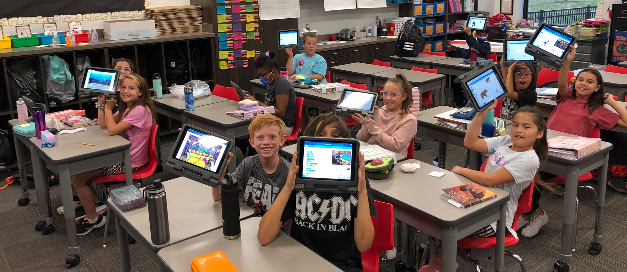 Students hold up iPads showing the games they programmed