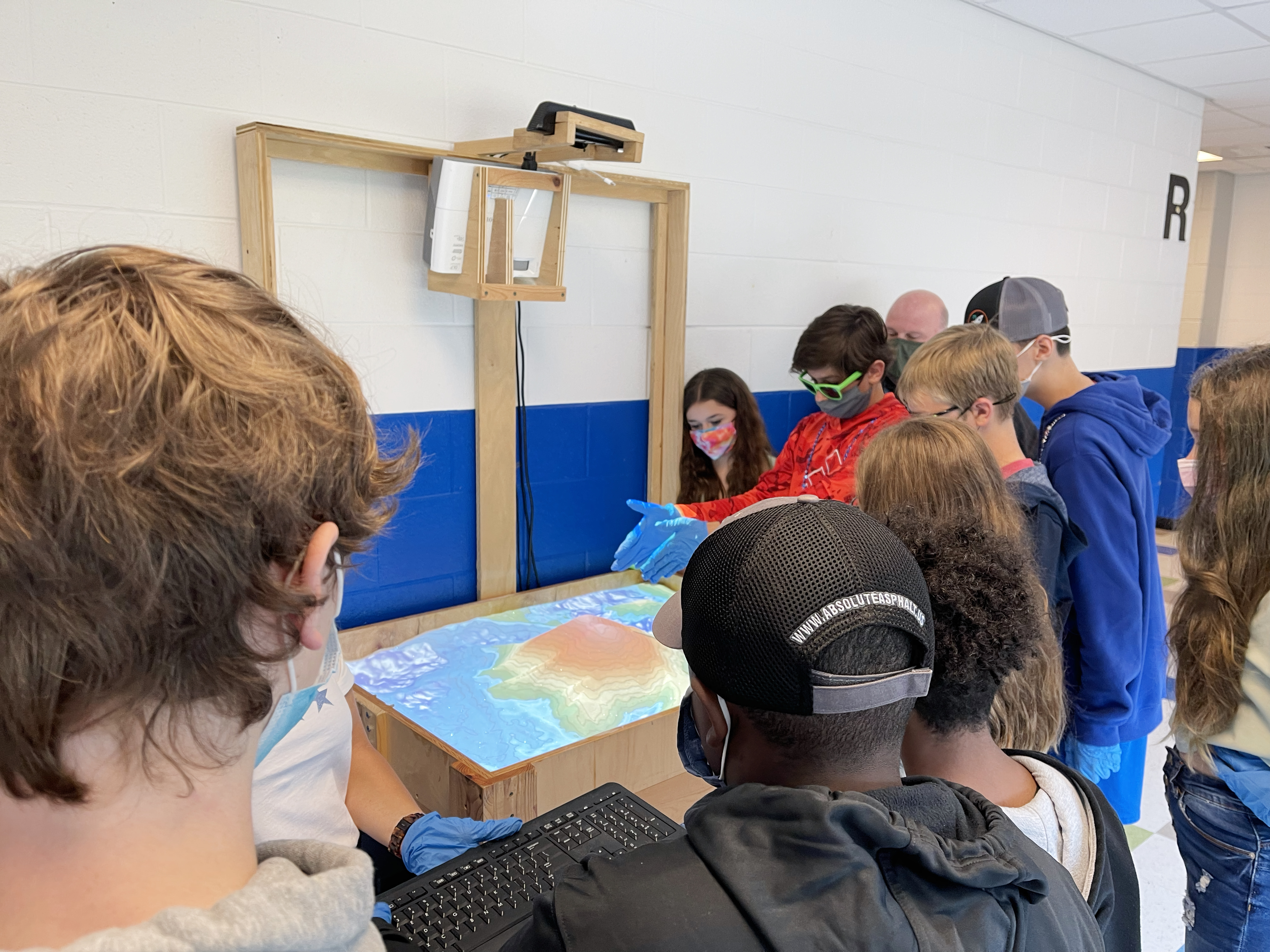 Middle school students working with the augmented reality sandbox